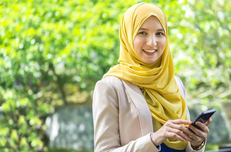 Mujer musulmán bastante joven que tiene una conversación sobre el teléfono imagen de archivo libre de regalías