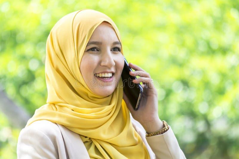 Mujer musulmán bastante joven que tiene una conversación sobre el teléfono fotos de archivo