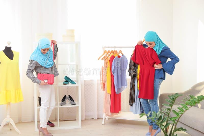 Mujer musulmán con su amigo que elige la ropa imagen de archivo