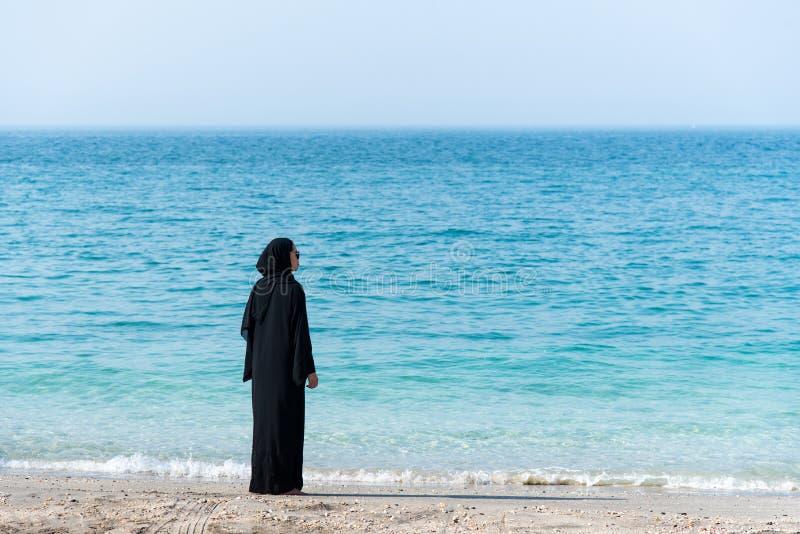 Mujer musulmán en abaya por la playa foto de archivo libre de regalías