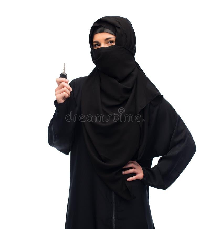 Mujer musulmán en hijab con llave del coche sobre blanco imágenes de archivo libres de regalías