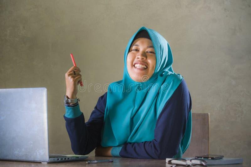 Mujer musulmán feliz y acertada joven del estudiante en el funcionamiento tradicional de la bufanda de la cabeza del hijab del Is foto de archivo libre de regalías