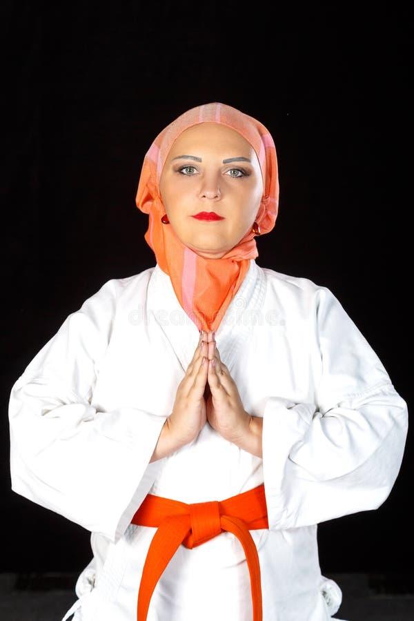 Mujer musulmán joven en kimono e hijab en el entrenamiento del karate sobre fondo negro Primer del tiroteo imagenes de archivo