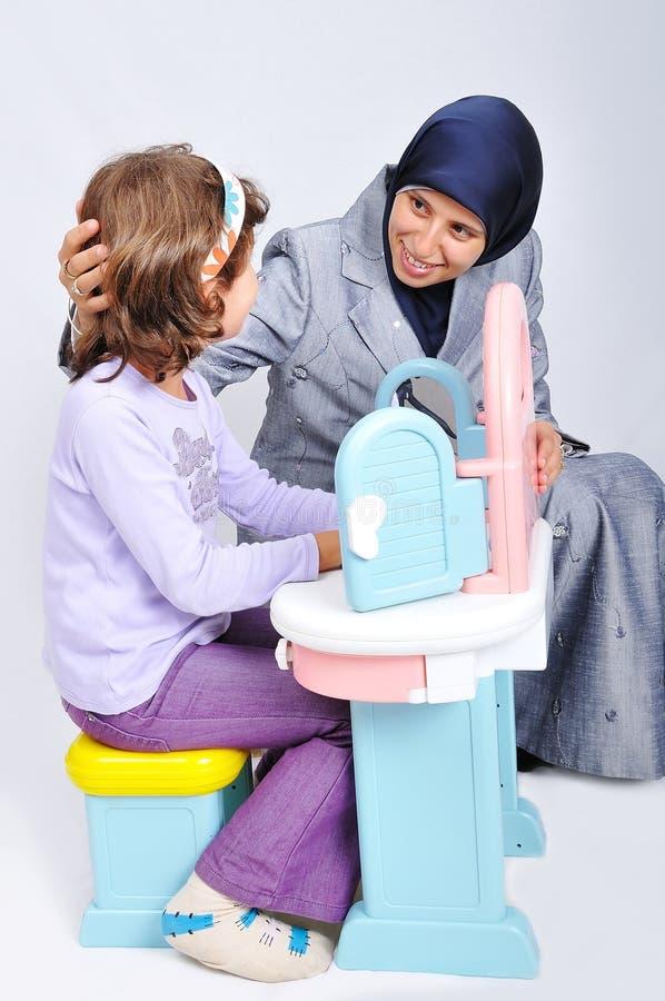 Mujer musulmán joven que juega y que aprende poco dau imagenes de archivo