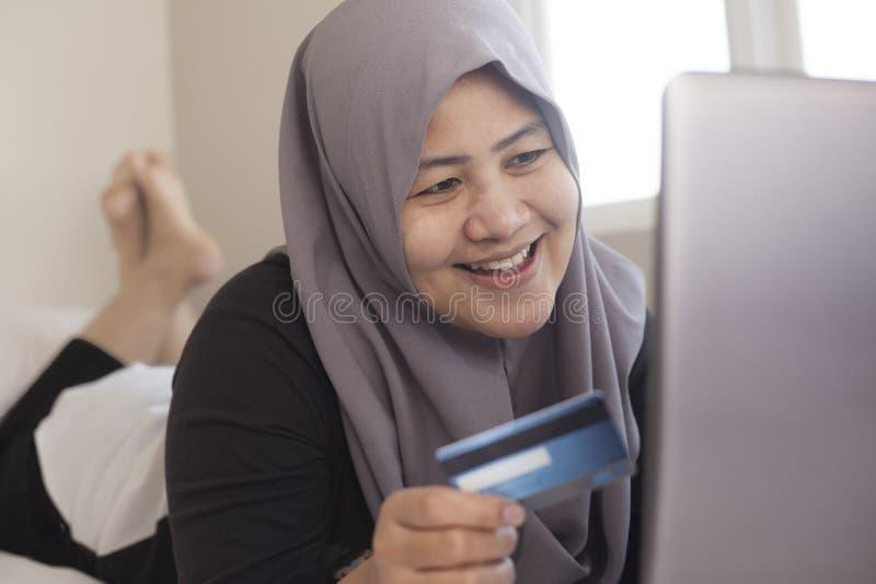 Mujer musulmán que hace la compra en línea imagen de archivo libre de regalías