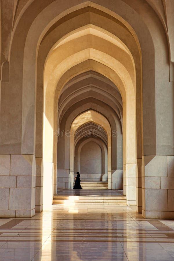 Mujer musulmán que recorre a través de arcos fotografía de archivo libre de regalías