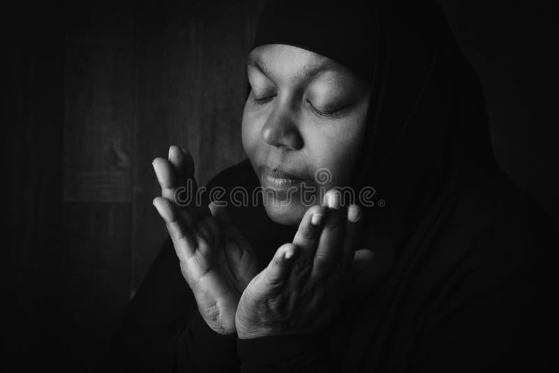 Mujer musulmán que ruega en blanco y negro fotografía de archivo