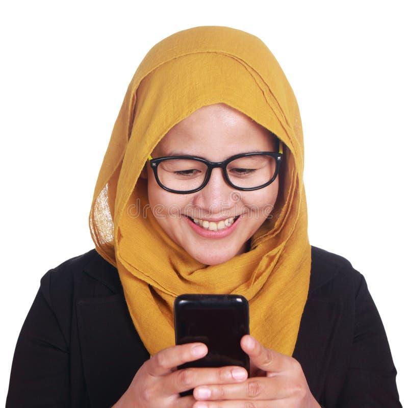 Mujer musulmán que sonríe mientras que lee el mensaje en el teléfono elegante fotos de archivo