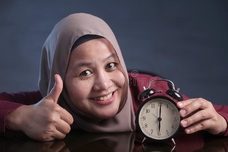 Mujer musulmán que sostiene un reloj foto de archivo