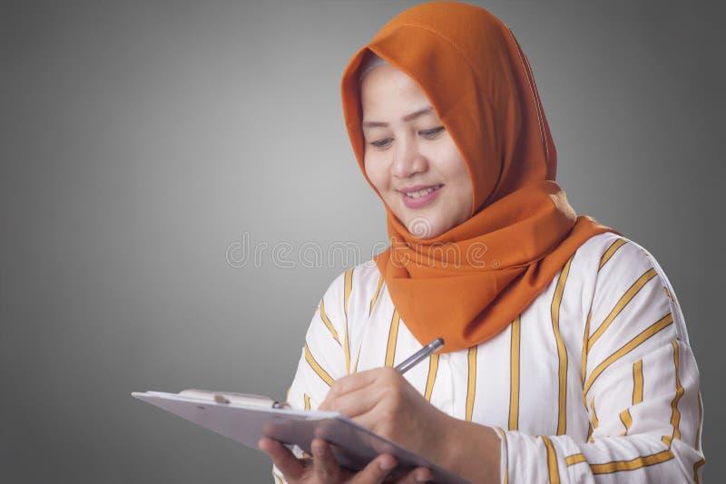 Mujer musulm?n que escribe algo imagen de archivo