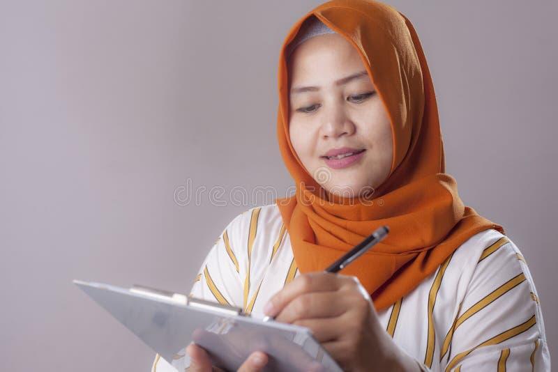 Mujer musulm?n que escribe algo foto de archivo