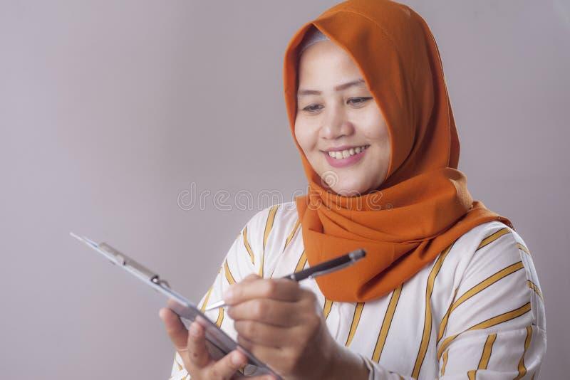 Mujer musulm?n que escribe algo fotos de archivo