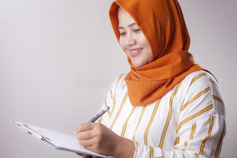 Mujer musulm?n que escribe algo imagenes de archivo