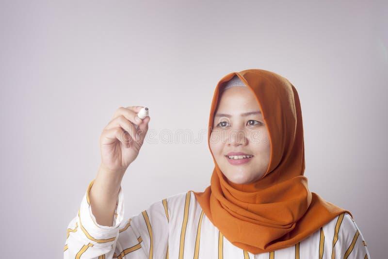 Mujer musulm?n que escribe en la pantalla virtual fotografía de archivo libre de regalías