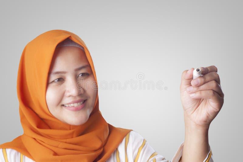 Mujer musulm?n que escribe en la pantalla virtual foto de archivo libre de regalías