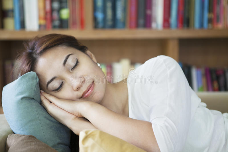 Mujer napping en el sofá imagen de archivo libre de regalías
