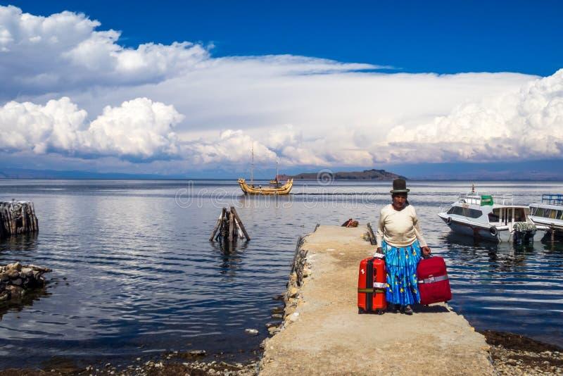Mujer nativa de los Andes bolivianos, en una cubierta con los bolsos rojos y barco del totora en el lago Titicaca, Bolivia imagenes de archivo