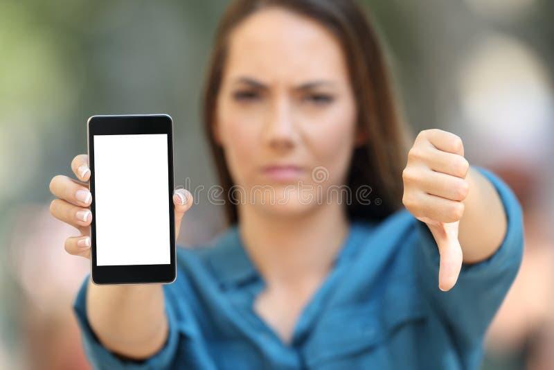 Mujer negativa que muestra una pantalla elegante en blanco del teléfono foto de archivo