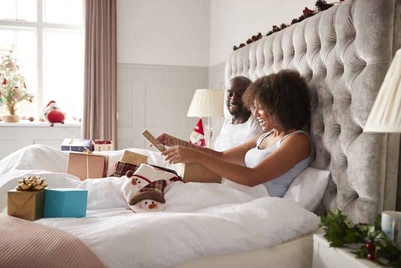 Mujer negra adulta joven que se sienta para arriba en cama el mañana de la Navidad con su socio que abre una actual, lateral vist foto de archivo