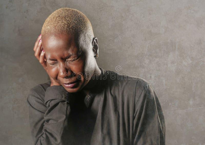 Mujer negra afroamericana triste y deprimida elegante joven que llora en la desesperación que se sostiene principal con las manos imagen de archivo libre de regalías