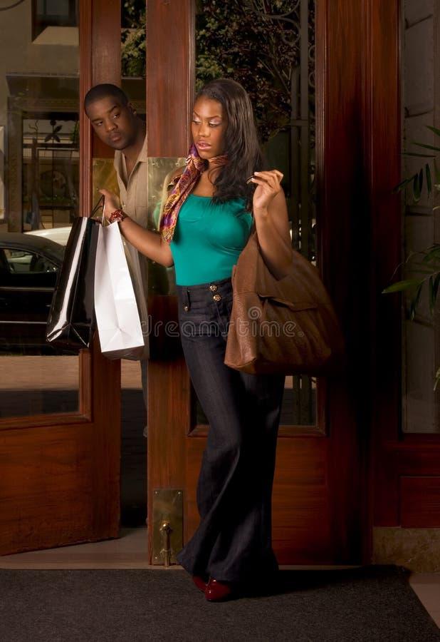 Mujer negra con el hombre de bolsos de compras que la mira foto de archivo libre de regalías