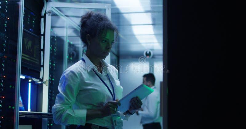 Mujer negra con la tableta que trabaja en sitio del servidor imagen de archivo libre de regalías