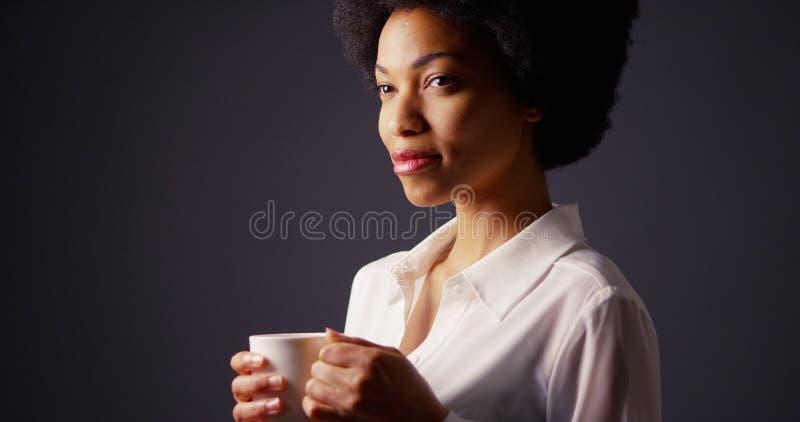 Mujer negra con la taza que se sostiene afro de café caliente y de sonrisa imagenes de archivo