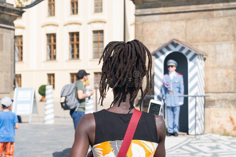 Mujer negra con los dreadlocks y turistas alrededor del castillo de Praga fotografía de archivo