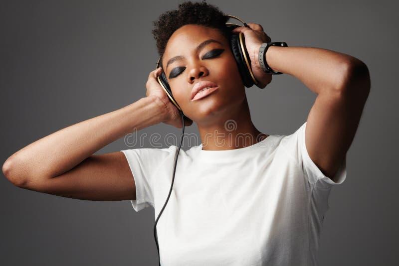 Mujer negra de la raza mixta en música que escucha de los auriculares fotografía de archivo libre de regalías