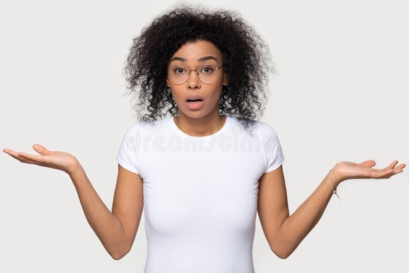 Mujer negra desconcertada dudosa confusa que encoge mirando la cámara imagen de archivo libre de regalías
