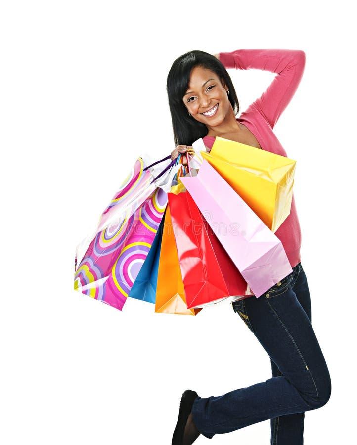 Mujer negra emocionada joven con los bolsos de compras foto de archivo