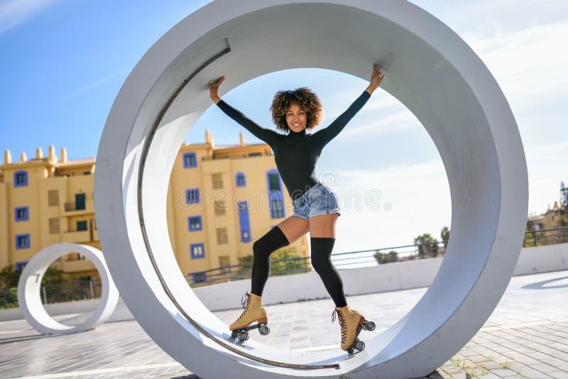 Mujer negra en los pcteres de ruedas que montan al aire libre en la calle urbana foto de archivo libre de regalías