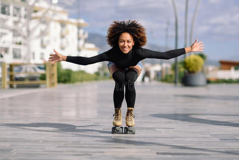 Mujer negra en los pcteres de ruedas que montan al aire libre en la calle urbana imagenes de archivo