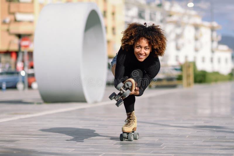 Mujer negra en los pcteres de ruedas que montan al aire libre en la calle urbana foto de archivo