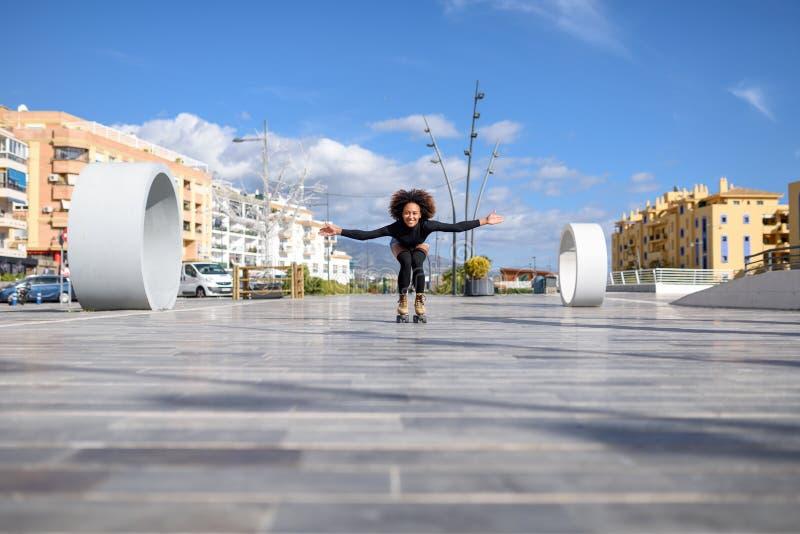 Mujer negra en los pcteres de ruedas que montan al aire libre en la calle urbana imagen de archivo libre de regalías