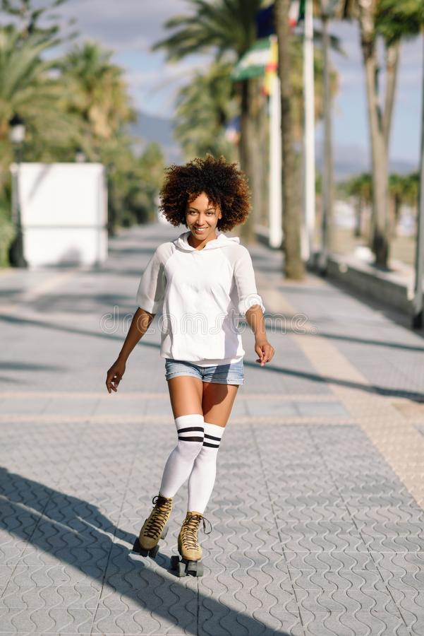 Mujer negra en los pcteres de ruedas rollerblading en 'promenade' de la playa con las palmeras imagen de archivo libre de regalías