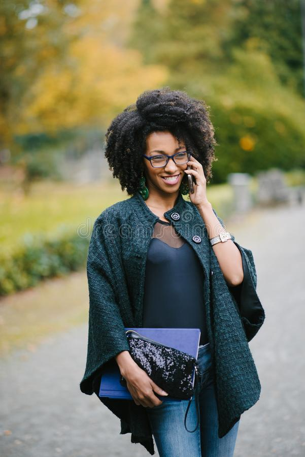 Mujer negra feliz durante una llamada de teléfono móvil en otoño fotografía de archivo