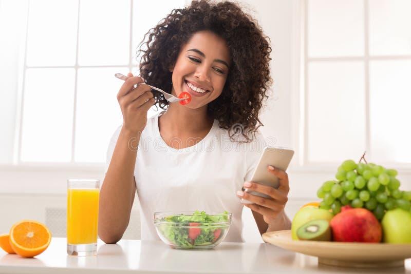 Mujer negra feliz que manda un SMS en smartphone mientras que come la ensalada imagen de archivo libre de regalías