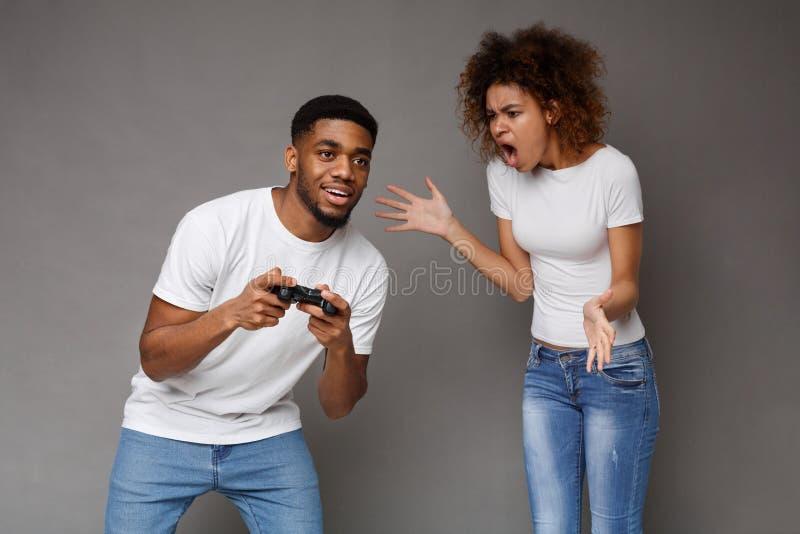 Mujer negra furiosa que grita en su novio que juega con la palanca de mando foto de archivo libre de regalías