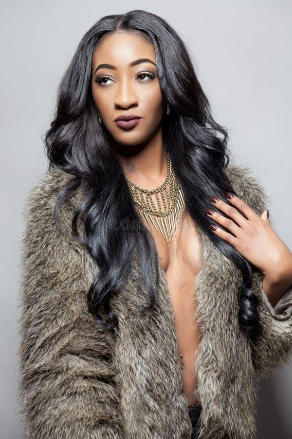 Mujer negra hermosa con el pelo rizado largo imagenes de archivo