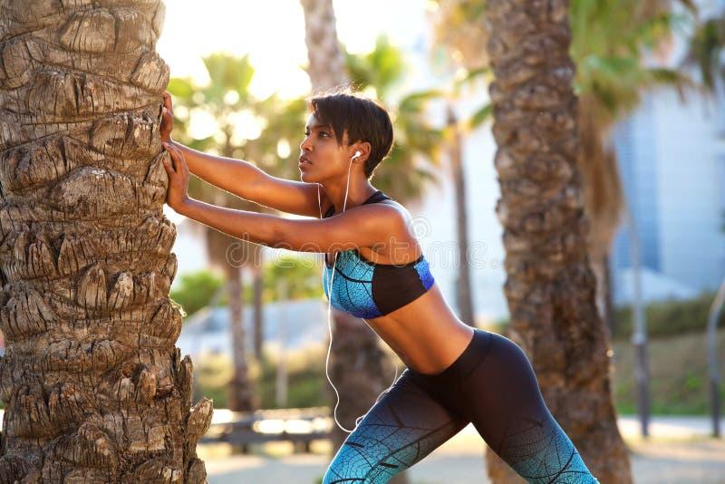 Mujer negra hermosa que estira rutina del entrenamiento foto de archivo