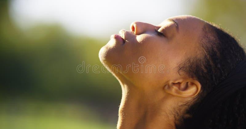 Mujer negra hermosa que siente el sol en su cara fotos de archivo