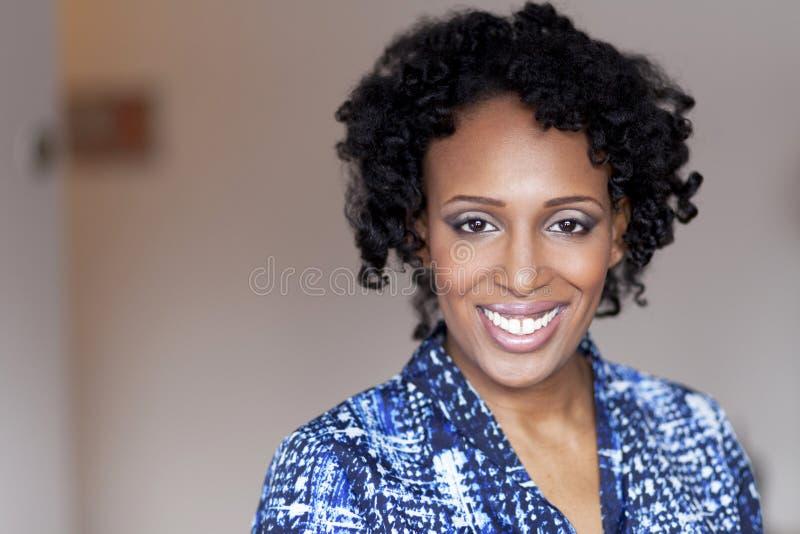 Mujer negra hermosa que sonríe en la cámara fotos de archivo