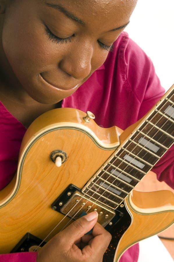 Mujer negra hispánica joven que toca la guitarra eléctrica imágenes de archivo libres de regalías