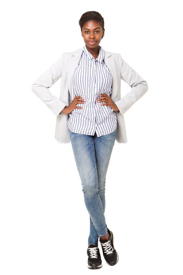 Mujer negra joven atractiva del cuerpo completo en la situación de la chaqueta contra el fondo blanco imagen de archivo