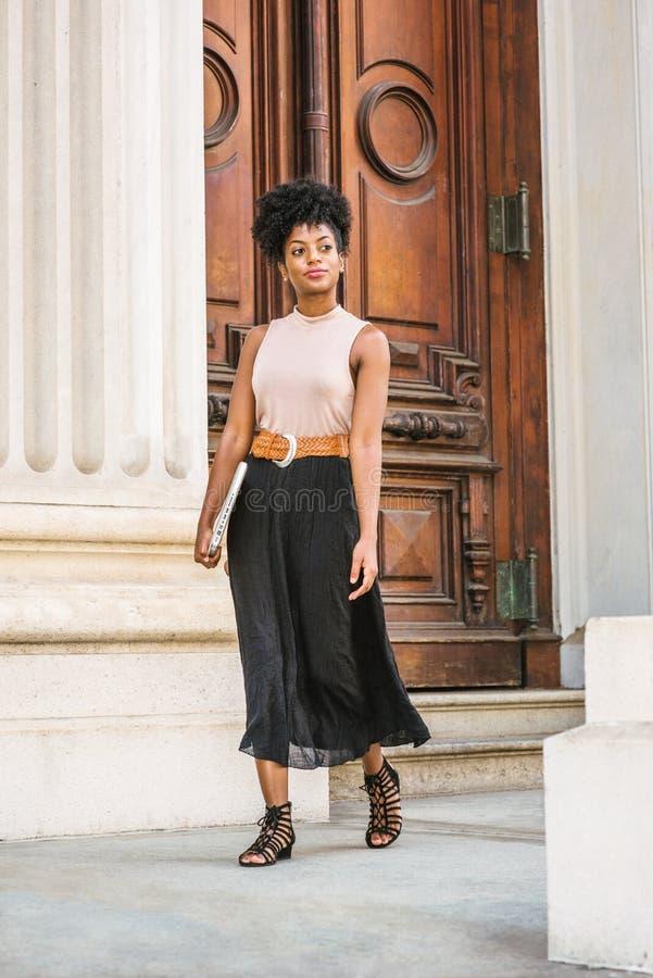 Mujer negra joven con el funcionamiento afro del peinado en Nueva York, top sin mangas del color claro que lleva, falda negra, co foto de archivo libre de regalías