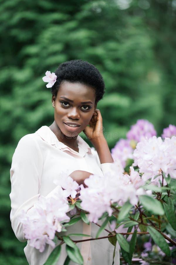 Mujer negra joven con el peinado afro en parque urbano Muchacha afroamericana que lleva la ropa casual entre las flores púrpuras fotos de archivo libres de regalías
