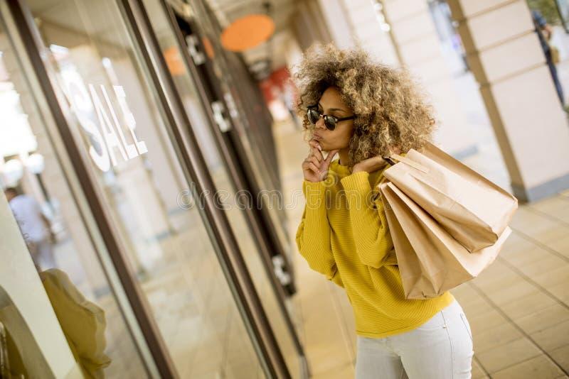 Mujer negra joven con el pelo rizado en compras imagen de archivo