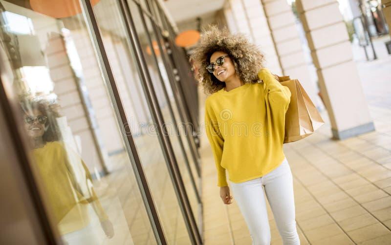Mujer negra joven con el pelo rizado en compras fotos de archivo libres de regalías