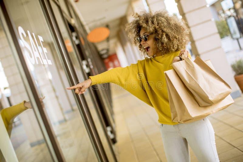 Mujer negra joven con el pelo rizado en compras fotos de archivo